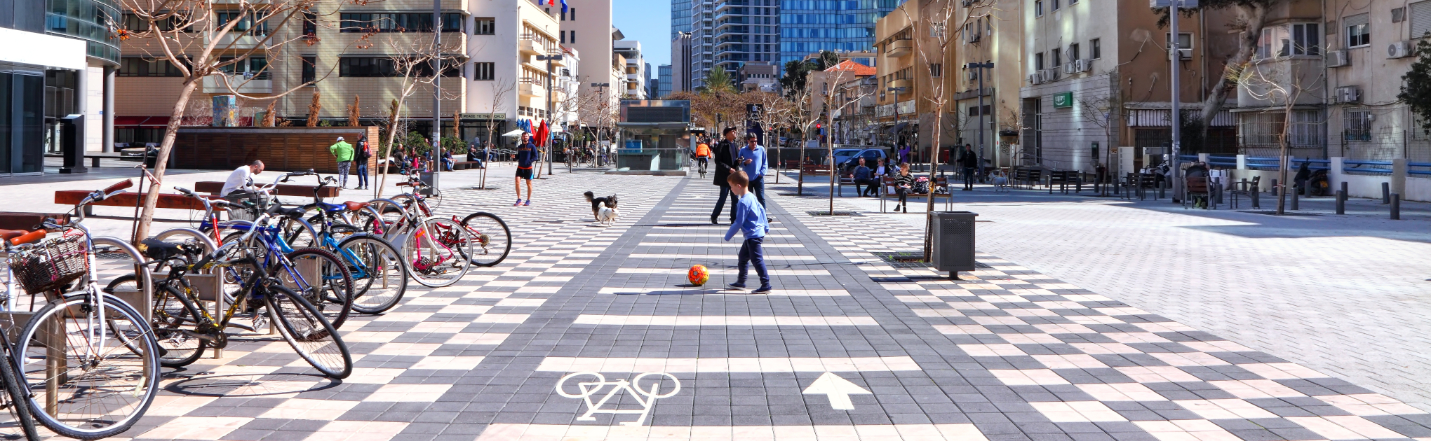 Cyclers children and pets inhabiting a paved square in Tel aviv