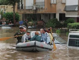 Elderly citizens being rescued by police in a boat from a flooded street in Israel