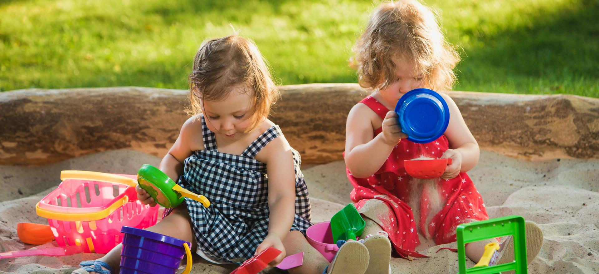 image of girls playing with plastic toys in sandbox
