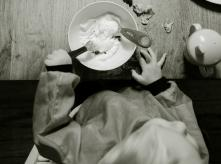 Black and White Photo of baby eating mash at a table