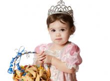Girl wearing a princess costume holding a basket of holiday treats