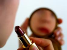 Woman is looking in the mirror and putting on lipstick