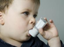 child holding asthma inhaler