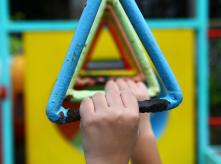 a hand of a child in a children's park