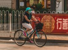 woman riding a bicycle wearing a protective mask in china