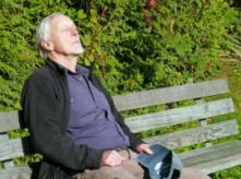 Older man sitting on a bench outside