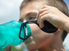 kid drinking water from a plastic bottle