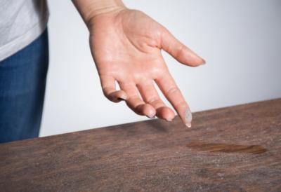 Finger picking up dust off of a table