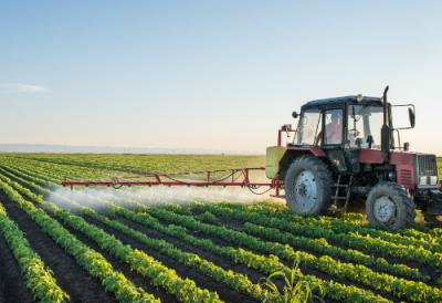 Image of tractor spraying pesticides in field
